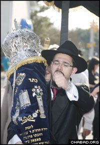 Rabbi Moshe Gourarie, co-director of the Chabad Jewish Center in Toms River, N.J., marches with the new Torah scroll.