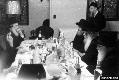At the festive meal following the fast of Yom Kippur, the Rebbe is sitting on the far right of the picture, his brother-in-law, Rabbi Shmaryahu Gurary, on the far left. The empty space at the head of the table is where Rabbi Yosef Yitzchak, the sixth Chabad Rebbe, would sit during his lifetime. (Photo: Agudas Chasidei Chabad Library)