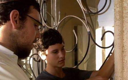 Installing a mezuzah on the front door.