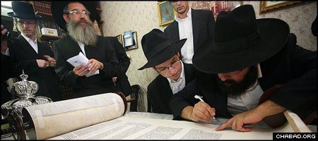 Descendents of Rabbi Aharon Mendel and Nechama Leah Hazan fill in letters of a Torah scroll written in their memory.