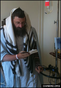 Rabbi Ephraim Simon prays in the hospital.