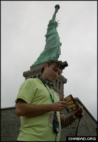 A Jewish man from Venezuela dons tefillin at the foot of the Statue of Liberty.