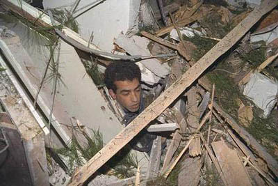 Following a direct hit from a scud missile on his home, an Israeli citizen emerges from the debris with no major wounds