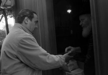 The Rebbe distributes honey cake, Lekach, on Hoshannah Rabbah (Photo: Levi Freidin/JEM)