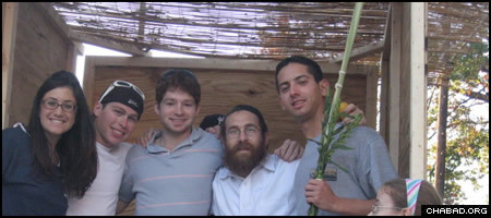 Rabbi Eli Backman, second from right, poses with students at the University of Maryland from the mobile sukkah operated by his Chabad House.