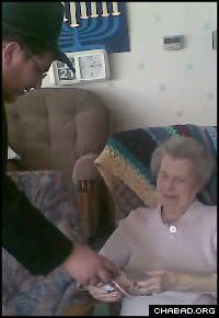 A volunteer from the Lubavitch yeshiva in Manchester gives a gift to a Jewish nursing home resident.