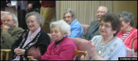 Residents of a Manchester, England, nursing home enjoy a performance by visiting yeshiva students.