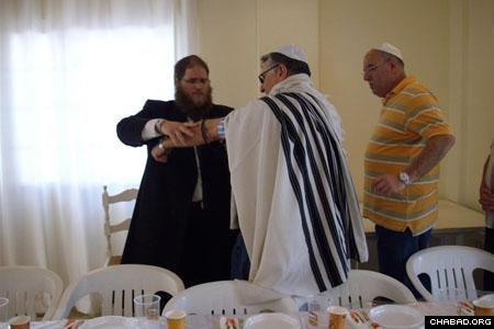 Rabbi Chaim Azimov assists one of the visitors to the Chabad center with their prayers.