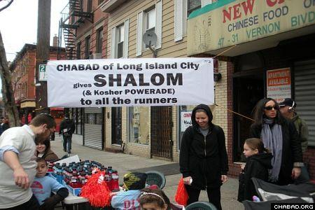 Spectators of the Nov. 1 New York City Marathon stand near a booth set up by Chabad-Lubavitch of Long Island City.