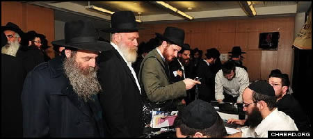 Newly-arrived Chabad-Lubavitch emissaries, such as Rabbi Moshe Rivkin from Beit Shemesh, Israel, second from left, register for their 25th annual conference in Brooklyn, N.Y. (Photo: Boruch Ezagui)