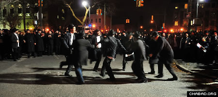 Chabad-Lubavitch emissaries dance at the intersection of Eastern Parkway and Brooklyn Avenue in Brooklyn, N.Y., Thursday night after joining in the completion of a Torah scroll in memory of Rabbi Gavriel and Rivka Holtzberg, the slain directors of the Mumbai, India, Chabad House. (Photo: Boruch Ezagui)