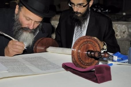 Rabbi Nachman Holtzberg, father of Gabi, fills in one of the final letters in the Litchfield Torah.