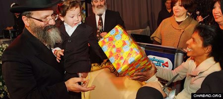 Indian nanny Sandra Samuel presents three-year-old Moshe Holtzberg, whom she saved from the carnage of Mumbai's Chabad House, with his birthday present.