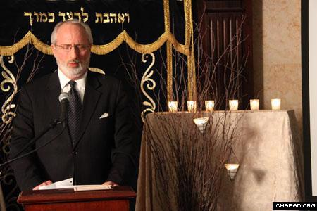Memorial candles glow as a cantor sings. (Photo: David Levi)