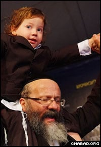 Rabbi Nachman Holtzberg of Brooklyn, N.Y., carries his grandson Moshe on his shoulders for a round of dancing on occasion of the little boy's third birthday.