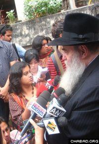 Rabbi Moshe Kotlarsky, vice chairman of the Chabad-Lubavitch educational arm, briefs reporters outside of Mumbai, India's Nariman House one year after terrorists stormed the Jewish center, and killed its directors, Rabbi Gavriel and Rivka Holtzberg, and four of their guests.