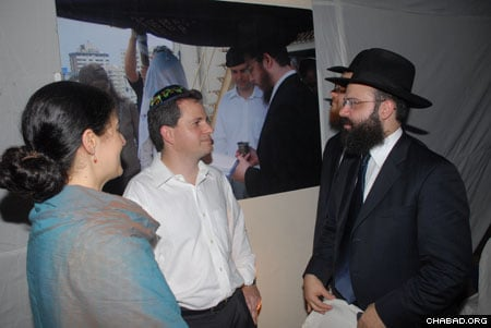 A couple whose wedding was officiated by Rabbi Gavriel Holtzberg speaks with Rabbi Avraham Berkowitz in front of a photo of their wedding.