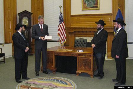 Rabbi Mendy Wineberg, left, presented a Jerusalem Stone Chanukah menorah to Kansas Gov. Mark Parkinson during a visit to the capitol with Rabbis Zalman Tiechtel and Yitzchak Itkin.