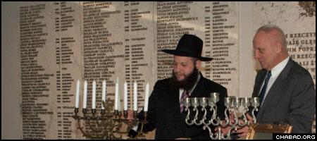 Chabad-Lubavitch Rabbi Shalom Ber Stambler kindles the Chanukah menorah with Polish Parliament Vice Marshal Stefan Niesiolowski.