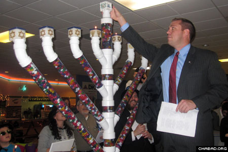 Town Supervisor Steve Neuhaus lights one of the candles on a menorah made out of jellybeans in Orange County, N.Y.