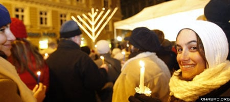 Attendees of a Chanukah menorah lighting in Budapest, Hungary, were encouraged to hold candles to symbolize the power of light over darkness.
