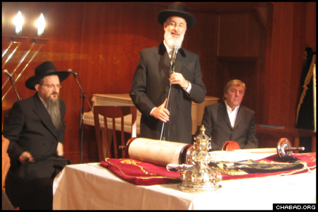 Flanked by Russian Chief Rabbi Berel Lazar, left, and donor Chaim Revitman, Israeli Chief Rabbi Yona Metzger addresses attendees of a Torah dedication ceremony at Moscow's Marina Roscha Synagogue.