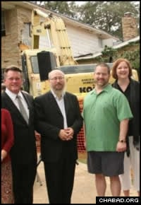 Rabbi Chaim Block stands with community members as the demolition gets underway.