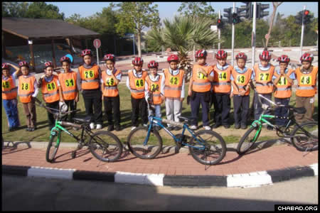 Students in Grades 4 through 6 from Ashkelon's Chabad-Lubavitch Ohr Menachem School ready their bikes for a run through a course operated by Israel's National Committee for Road Safety.