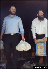 Assisted by a rabbinical student, Chabad-Lubavitch Rabbi Shimon Pelman, right, distributes food to earthquake survivors.