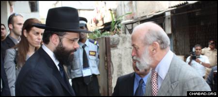 Rabbi Avraham Berkowitz greets Prince Michael of Kent outside the heavily-damaged Chabad-Lubavitch of Mumbai, India, has Israeli Consul Gen. Orna Sagiv looks on.
