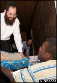 L'émissaire 'Habad-Loubavitch Rav Shimon Pelman distribue des vivres à des survivants du tremblement de terre. (Photo: Marc Asnin/Chabad.org)