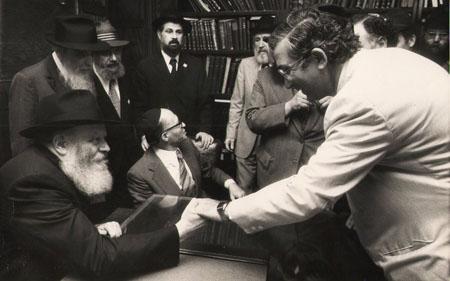 Dan Patir and the Rebbe conversing during Prime Minister Menachem Begin's (sitting center) visit.