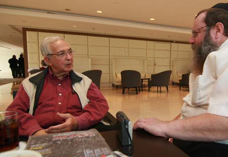 Yitzchak Yehudah Holtzman listens as Dan Patir describes his visits at Lubavitch World Headquaters. (Photo: Kfar Chabad Magazine)