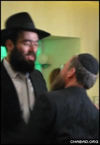 Rabbi Arie Zeev Raskin, left, greets a dinner guest.