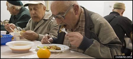 Seniors eat a hot meal at one of Colel Chabad's soup kitchens in Safed, Israel.