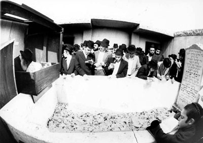 The Rebbe (far left) at the resting place of the sixth Lubavitch Rebbe, Rabbi Yosef Yitzchak Schneersohn, of righteous memory.