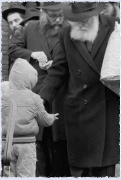 The Rebbe exiting 770 on that morning, distributing coins to the children to give to charity.