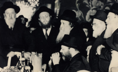 The Rebbe, of righteous memory, says a discourse on Chabad philosophy. Traditionally the crowd stands during the recital of a discourse, on the extreme left is Rabbi Shmaryahu Gurary, of blessed memory, the Rebbe's brother-in-law. (Photo courtesy of the Shafran family in memory of Rabbi Benzion Shafran)