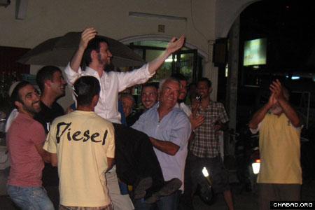 Jewish residents and tourists dance with Chabad-Lubavitch Rabbi Shimon Binshtock in Phuket.