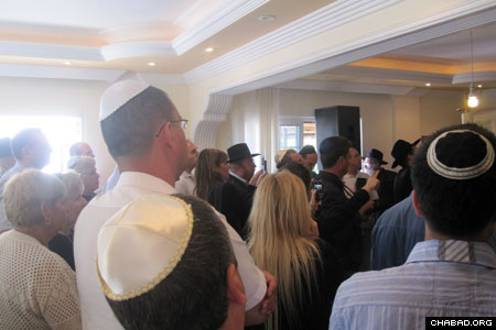 Congregants at Chabad-Lubavitch of North Cyprus in Kyrenia stand as the center's new Torah scroll is readied for its dedication.