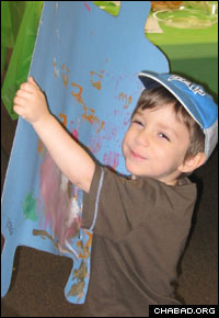 A student at the Torah Troopers preschool holds a Torah-shaped poster he decorated for the holiday of Shavuot, which celebrates the giving of the Torah.