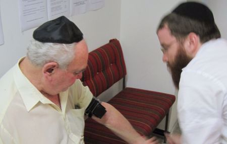 Wrapping tefillin on an elderly gentleman in the JCC.