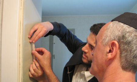 Helping Boris affix a mezuzah on his door.