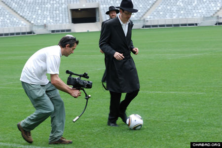 Rabbi Pini Hecht, Outreach Director of Camps Bay Shul, stays on top of the ball during a lighthearted match between a group of Chabad-Lubavitch rabbis – calling themselves Chabad United – and the Ikapa Sporting Football Club. The February face off took place in Cape Town Stadium, one of the hosting venues of the 2010 World Cup. (Photo: Leif Johannson Photography / Shawn Levin Productions)