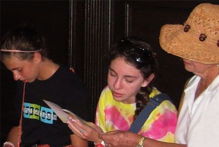 Chana and Nechama (from Mexico) read the Shema with their grandma as their grandfather puts on tefillin.
