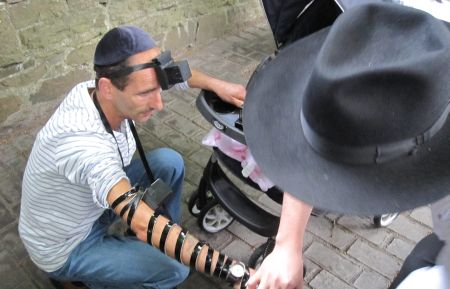 Patrick donning tefillin as his baby watches.