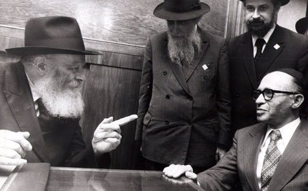 The Rebbe – pointing to the large contingent of photographers, reporters and TV crews – tells Prime Minister Menachem Begin that reporters are integral to democracies. (Photo: Eliyahu Attar/Dan Patir/Kfar Chabad Magazine)