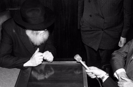 The Rebbe responds to the reporters, explaining that he gives his blessings to the Prime Minister as he travels to Washington. (Photo: Velvel Schildkraut (Michele) Studios/Kahn family)