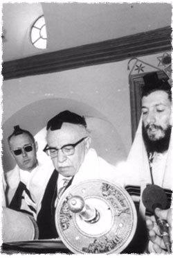 """Mr. Kalms (left) at the reading of the Torah, in the """"Tzemach Tzedek Shul,"""" as President of Israel Zalman Shazar makes the blessing on the Torah."""