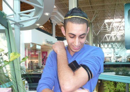 One of the Israelis in the mall putting on tefillin.